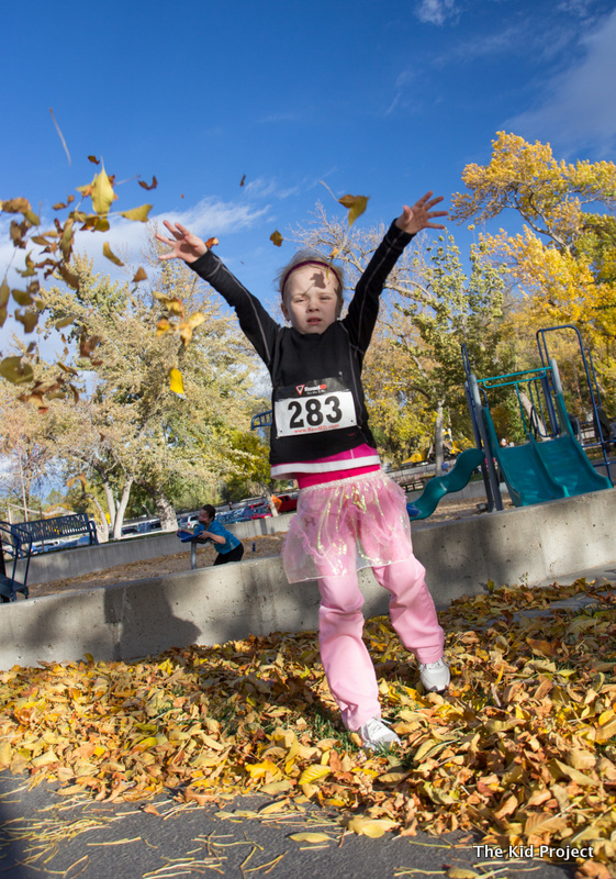 girl tossing leaves