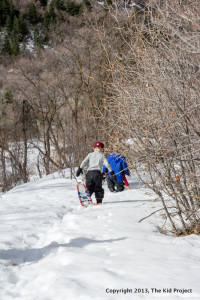 Boys snowshoe in forest