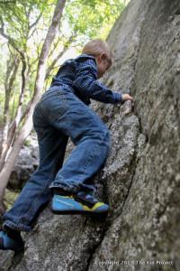 Boy bouldering , climbing