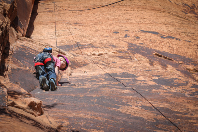 Girl climbing Seibernetics near Moab, UT