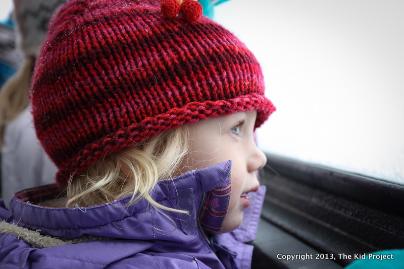 Toddler looking out window of tram