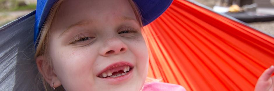 Little girl camping in hammock
