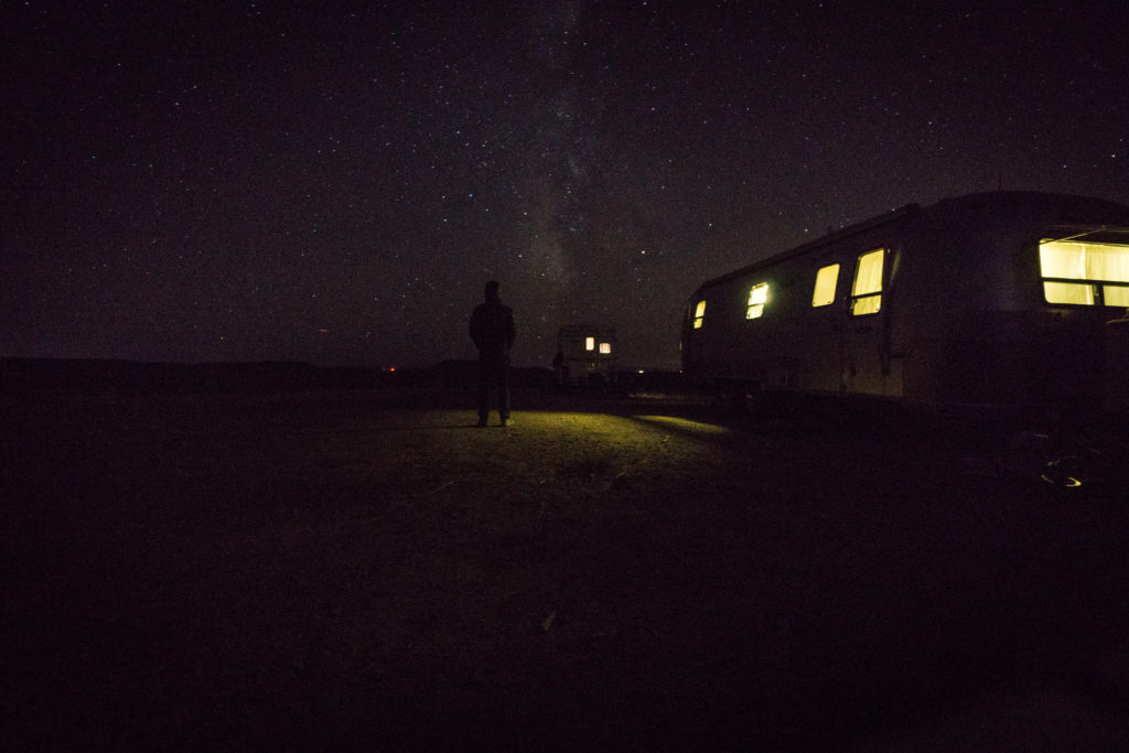 Lit up Airstream under the constellations